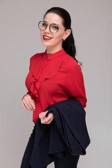 Portrait vertical d'une belle fille dans des vêtements de travail lumineux isolés sur un fond clair