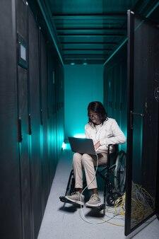 Portrait vertical complet d'une femme afro-américaine handicapée utilisant un ordinateur portable tout en travaillant dans la salle des serveurs, opportunité d'emploi accessible