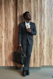 Portrait vertical complet d'un homme d'affaires afro-américain réussi regardant loin en se tenant debout sur fond de bois