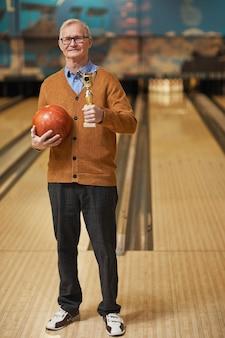 Portrait vertical complet d'un homme senior souriant tenant un trophée et une boule de bowling tout en posant au bowling après avoir remporté le match, espace de copie