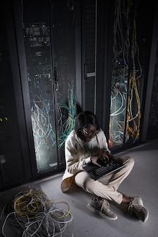 Portrait vertical complet d'une jeune femme afro-américaine assise sur le sol dans la salle des serveurs et utilisant un ordinateur portable tout en travaillant avec un superordinateur dans un centre de données, espace de copie
