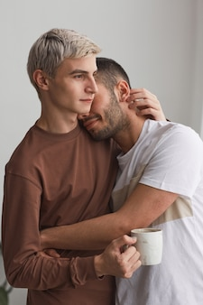 Portrait vertical d'un couple gay contemporain embrassant tendrement à l'intérieur dans des tons minimes