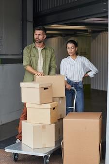 Portrait vertical de couple moderne debout par chariot avec des boîtes en carton lors du chargement de l'unité de stockage