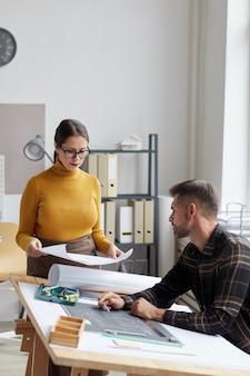 Portrait vertical de deux architectes discutant de plans tout en travaillant ensemble au bureau