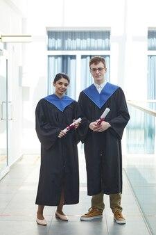 Portrait vertical de deux jeunes gens portant des robes de graduation et regardant la caméra tout en se tenant à l'intérieur dans un intérieur universitaire moderne
