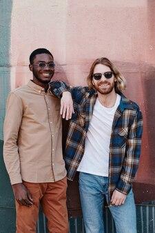 Portrait vertical de deux jeunes hommes contemporains posant à l'extérieur et souriant à la caméra tout en portant des lunettes de soleil
