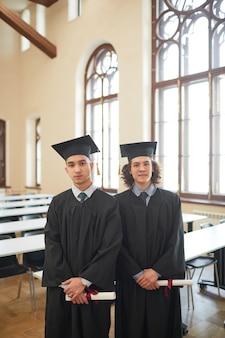 Portrait vertical de deux jeunes hommes portant une robe de cérémonie et regardant la caméra tout en posant dans l'auditorium de l'école pendant l'obtention du diplôme