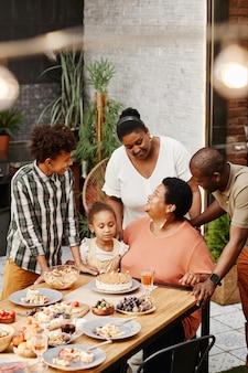 Portrait vertical d'une femme afro-américaine âgée célébrant son anniversaire en famille et soufflant des chandelles...