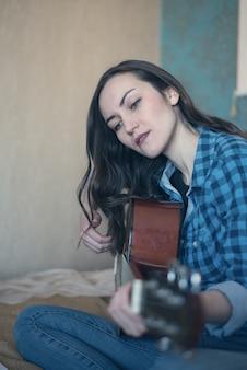 Portrait vertical d'une femme engagée dans l'enseignement de la guitare acoustique sur le lit dans la chambre