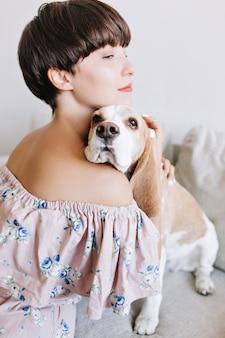 Portrait vertical de femme gracieuse légèrement bronzée tenant doucement son chien beagle sur mur blanc