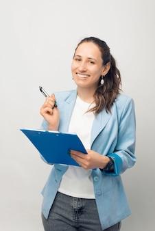 Portrait vertical d'une femme souriante et confiante qui tient un presse-papiers.