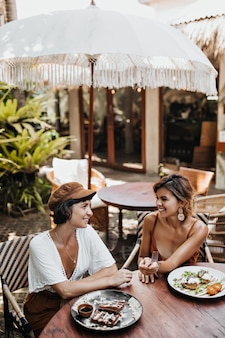 Portrait vertical de femmes bronzées dans des vêtements à la mode souriant et parlant dans un café de rue confortable