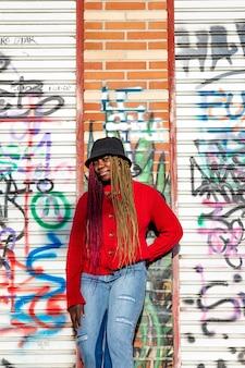 Portrait vertical d'une fille noire exotique avec des tresses colorées. habillé d'un pull rouge et d'un chapeau noir. fond de mur de graffiti