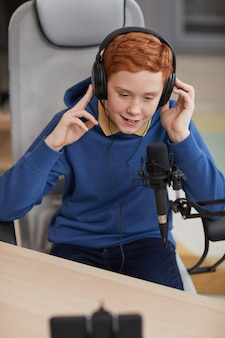 Portrait vertical en grand angle d'un adolescent aux cheveux rouges parlant au microphone et enregistrant une vidéo en streaming en ligne