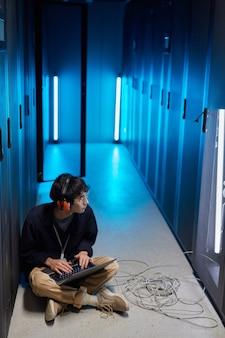 Portrait vertical en grand angle d'un jeune homme asiatique assis sur le sol dans la salle des serveurs éclairée par la lumière bleue lors de la configuration du réseau de superordinateurs via un ordinateur portable, espace de copie
