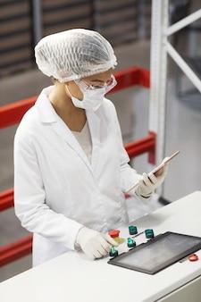 Portrait vertical en grand angle d'une travailleuse appuyant sur les boutons du panneau de commande tout en faisant fonctionner des unités de machine dans une usine chimique moderne