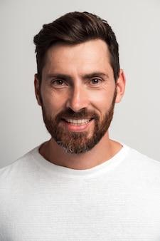 Portrait vertical de l'heureux bel homme barbu debout et souriant gai à la caméra. prise de vue en studio intérieur, isolé sur fond blanc