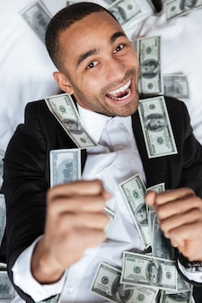 Portrait vertical de l'homme africain en costume couché avec de l'argent sur le lit dans la chambre d'hôtel. vue de dessus. fermer