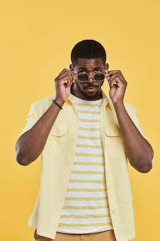 Portrait vertical d'un homme afro-américain à la mode portant des lunettes de soleil et regardant la caméra en se tenant debout...