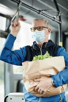 Portrait vertical d'un homme âgé portant un masque dans un bus lors d'un voyage en transports en commun et tenant une balustrade