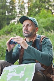 Portrait vertical d'homme mûr tenant des jumelles et une carte lors d'une randonnée seul en forêt