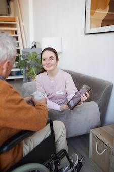 Portrait vertical d'une infirmière souriante parlant à un homme âgé en fauteuil roulant tout en utilisant une tablette numérique à la maison de retraite