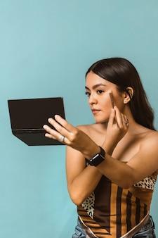 Portrait vertical de jeune femme latino-américaine heureuse et belle appliquant le maquillage de visage