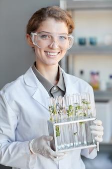 Portrait vertical de jeune femme scientifique souriant caméra t tout en tenant des tubes à essai avec des échantillons de plantes en laboratoire de biotechnologie