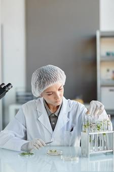 Portrait vertical de jeune femme scientifique tenant un tube à essai avec des échantillons de plantes tout en travaillant sur la recherche en laboratoire de biotechnologie, espace copie