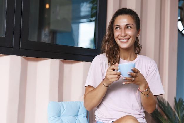 Portrait vertical d'une jeune fille souriante détendue, boire du thé sous le porche.