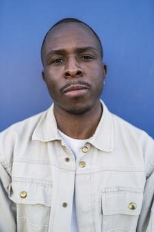 Portrait vertical d'un jeune homme noir sur bleu