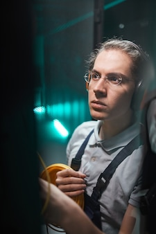 Portrait vertical d'un jeune ingénieur réseau connectant les câbles dans la salle des serveurs pendant les travaux de maintenance dans le centre de données