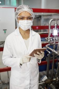 Portrait vertical d'une jeune travailleuse portant des vêtements de protection et regardant la caméra tout en utilisant une tablette dans une usine chimique