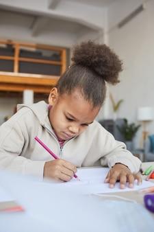 Portrait vertical d'une jolie fille afro-américaine dessinant des images assise à table dans un intérieur confortable, espace pour copie