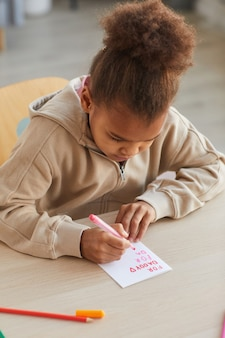 Portrait vertical d'une jolie fille afro-américaine faisant une carte faite à la main comme cadeau pour la fête des pères, espace pour copie