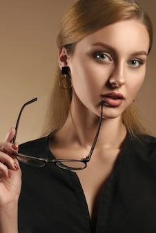 Portrait vertical de jolie fille prenant des lunettes et portant une chemise noire