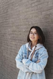 Portrait vertical d'une jolie jeune fille aux cheveux courts, portant des lunettes et des vêtements de style urbain, appuyée sur un mur de briques.