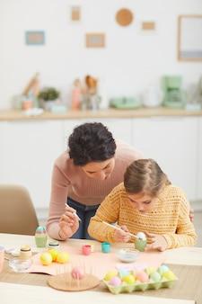 Portrait vertical de la mère et la fille de la peinture des oeufs de pâques ensemble assis à table dans un intérieur de cuisine confortable, espace copie