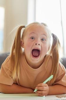 Portrait vertical de mignonne petite fille atteinte du syndrome de down grimaçant à la caméra heureusement avec la bouche ouverte tout en écrivant ou en dessinant pendant la classe de développement