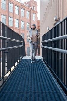Portrait vertical de pleine longueur d'une femme moderne du moyen-orient se réveillant vers la caméra en ville