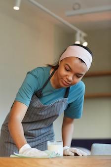 Portrait vertical d'une table de nettoyage de jeune serveuse métisse dans un café ou un café lors de la préparation de l'ouverture le matin