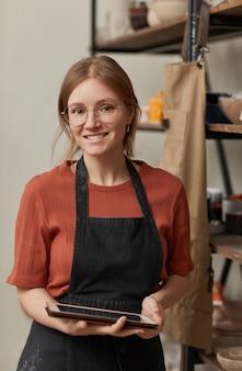 Portrait vertical à la taille d'une jeune artisan tenant une tablette et souriant à la caméra tout en gérant une petite entreprise dans un atelier de poterie