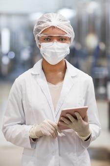 Portrait vertical à la taille d'une jeune femme travaillant dans une usine chimique et regardant la caméra tout en portant des vêtements de protection