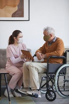 Portrait vertical de toute la longueur d'une jeune infirmière aidant un homme âgé en fauteuil roulant à l'aide d'une tablette numérique à la maison de retraite, tous deux portant des masques