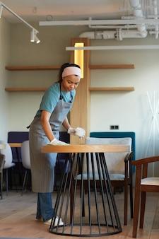 Portrait vertical de toute la longueur d'une jeune table de nettoyage de serveuse métisse dans un café ou un café tout en se préparant à l'ouverture le matin, espace de copie