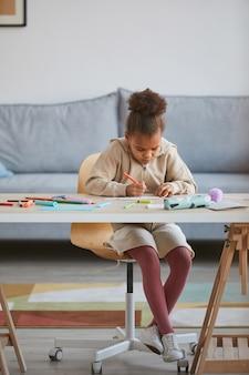 Portrait vertical de toute la longueur d'une jolie fille afro-américaine dessinant assis à table dans un intérieur confortable, espace pour copie
