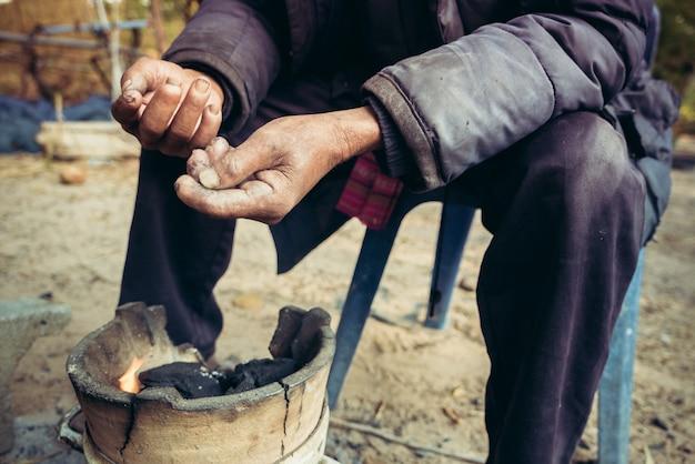 Portrait de vieil homme sur une campagne de la thaïlande en hiver avec la petite cheminée