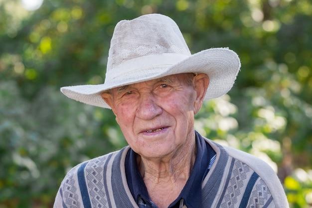 Portrait d'un vieil homme dans un chapeau blanc sur un arrière-plan flou_