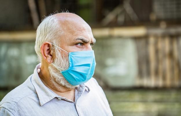 Portrait d'un vieil homme dans un masque médical.