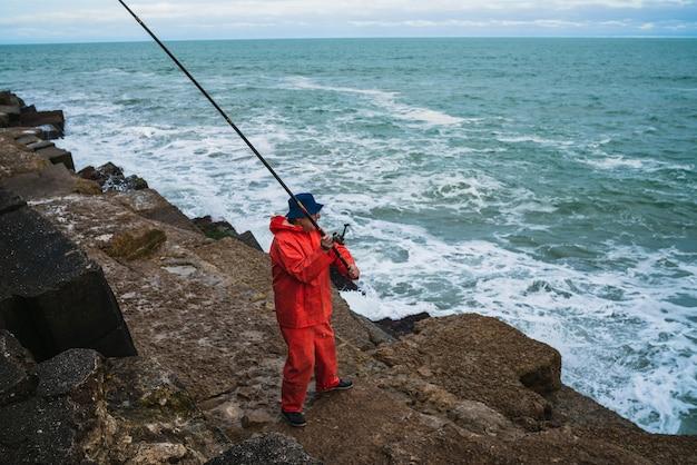 Portrait d'un vieil homme pêchant dans la mer. concept de pêche.